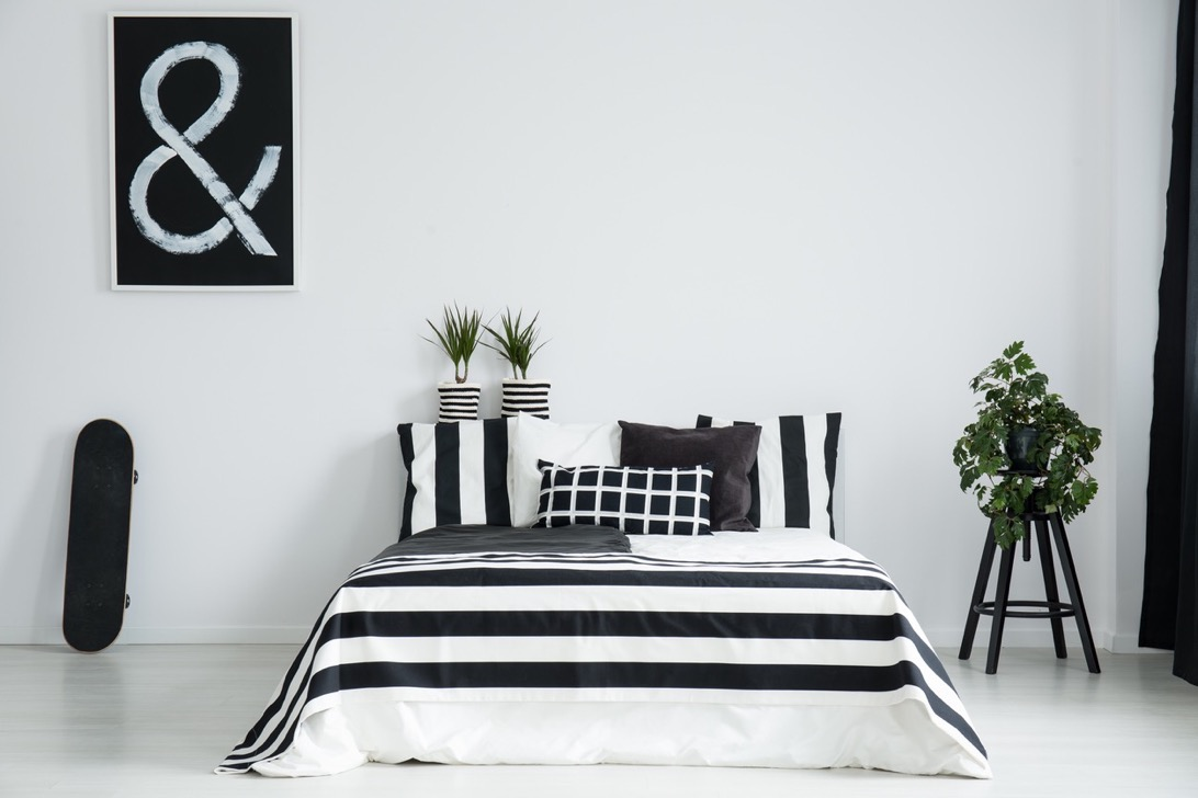 King-size bed between skateboard and plant on wooden stool in simple black and white bedroom